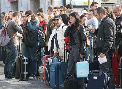Foto tratta da El Periodico: viaggiatori provenienti da Valencia aspettano un autobus a Tarragona per raggiungere Barcellona